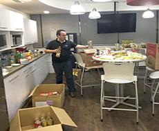 Ciena volunteer standing in breakroom with cartons of food