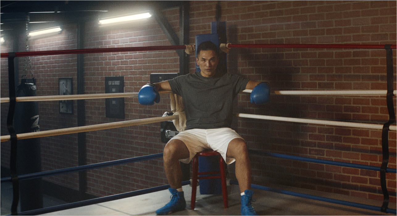 Man seating at the corner of a ring in the gym